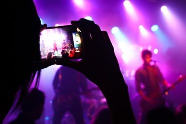 person recording concert on phone